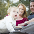Cute Child Looks Up to Sky as Young Parents Smile — Stock Photo #7951390