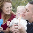 Young Parents Blowing Bubbles with their Child Boy in Park — Stock Photo #7951395