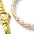 Golden wrist watch and necklace — Stock Photo