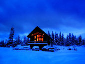 Winter cabine at night met gloeiende warme windows — Stockfoto