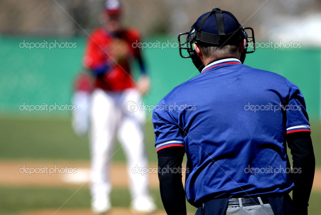 Baseball player wearing uniform throwing baseball with umpire  Stock Photo #7959375