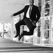 Happy young businessman clicking his heels - Foto Stock