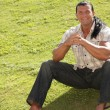 Happy man sitting on the grass - Stockfoto