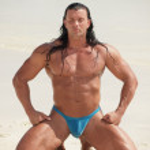Bodybuilder meditating on the beach — Stock Photo #7006127