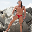 Bodybuilder posing on the rocks — Stock Photo