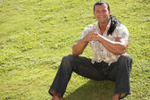 Happy man sitting on the grass — Stock Photo