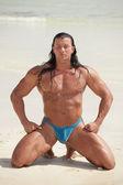 Bodybuilder meditating on the beach — Stock Photo