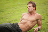 Handsome man laying on the grass — Stock Photo