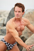Bodybuilder on the rocks — Stock Photo