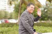Businessman smiling and waving — Stock Photo