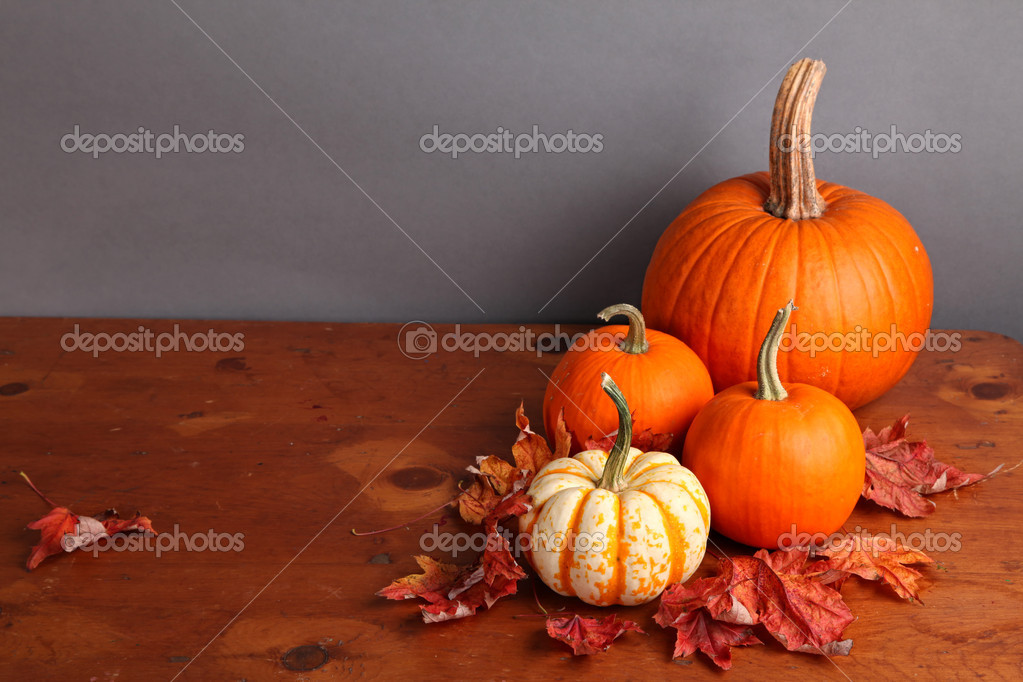 Fall pumpkin and decorative squash with autumn leaves on a wooden table.  Stockfoto #6787419