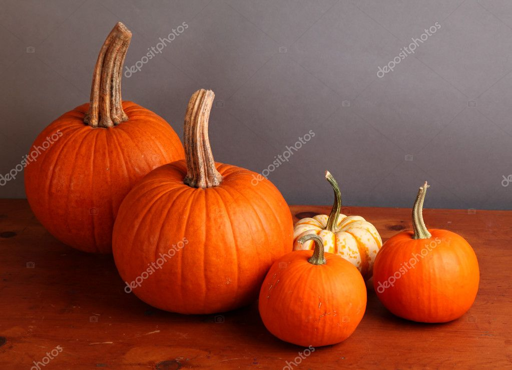 Fall pumpkin and decorative squash with autumn leaves on a wooden table.   #6787479