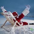 Santa relaxing on a sunbed — Stockfoto