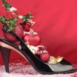 Ladies shoes with christmas decorations over red background — Stock Photo