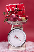 Christmas decorations on weighing sclaes cost concept — ストック写真