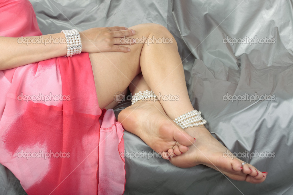 Woman legs wearing pink dress over grey satin fabric  Stock Photo #6846549
