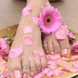 Female feet with rose petals and flowers — Photo #7427089