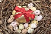 Uova di pasqua dorata nel nido di uccello sopra bianco — Foto Stock
