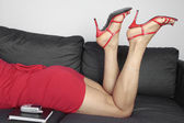 Beautiful female legs wearing red heels and dress relaxing — Stock Photo