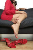 Beautiful female legs take off high heels relaxing — Stock Photo