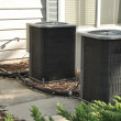 Two outdoor central air conditioner units - Stock Photo