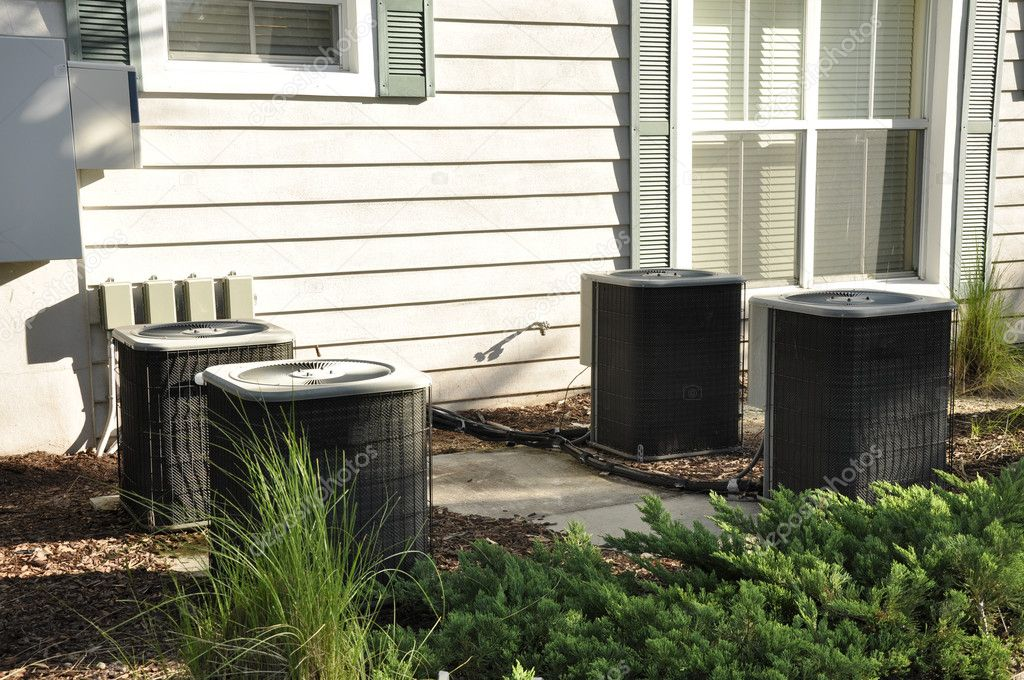 Several outdoor central air conditioning units by a building — Stock Photo #6839291