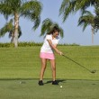 Teenage girl golfing - Stock Photo