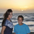 Teen brother and sister by beach at sunset — Stock Photo