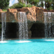 Stock Photo: Waterfalls by inground swimming pool
