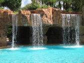 Waterfalls by inground swimming pool — Stock Photo