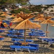 Greek beaches of white sand and stone, with cafes and beach umbrellas of pa — Stock Photo