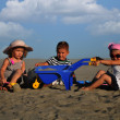 Two girls and a boy playing on the beach sand — Stock Photo #7882632