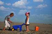 Girls and a boy playing on the beach sand — Stock Photo