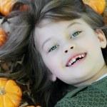 bambino sdraiato in foglie di autunno — Foto Stock