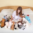 Royalty-Free Stock Photo: Girl reading in bed with toys