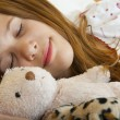 Young teenage girl sleeps peacefully with her favorite childhood toys besid — Stock Photo #7137645
