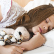 Young teenage girl sleeps peacefully with her favorite childhood toys besid — Stock Photo #7137669