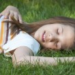 Pretty young teenage girl resting on the bed of grass. - Stock Photo