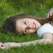Pretty young teenage girl resting on the bed of grass and smiling. - Stock Photo