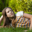 Pretty young teenage girl resting on the bed of grass - Stock Photo