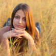 Beautiful teenage girl lies in the meadow on sunny autumn day. - Stock Photo