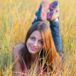 Beautiful smiling young girl lies in the grass on sunny autumn day. - Stock Photo