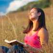 Beautiful young girl enjoys sun while sitting on the meadow and reading the - Stock Photo