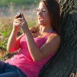 Beautiful teenage girl laughs while reading the message on the mobile phone — Stock Photo