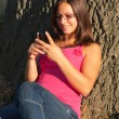 Beautiful teenage girl laughs while reading the message on the mobile phone - Stock Photo