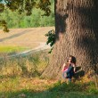 Beautiful young girl enjoys sun while sitting under the huge oak tree and r — Stock Photo