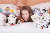 Girl lying on the bed with toys — Stock Photo
