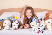 Girl in the bed with toys — Stock Photo