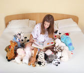 Girl reading in bed with toys — Stock Photo