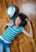 Teenage girl lies on the floor and listens to the music — Stock Photo
